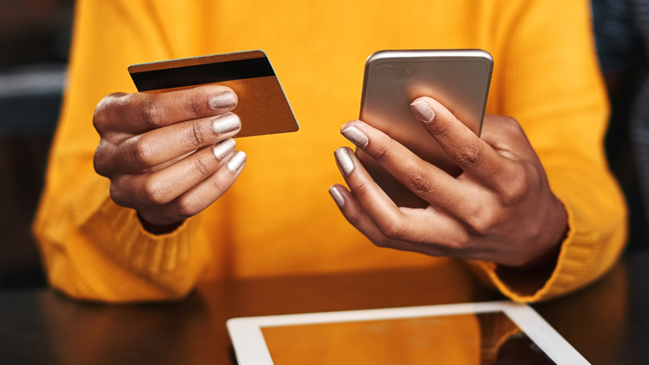 A lady in a yellow shirt holding a phone and a credit card